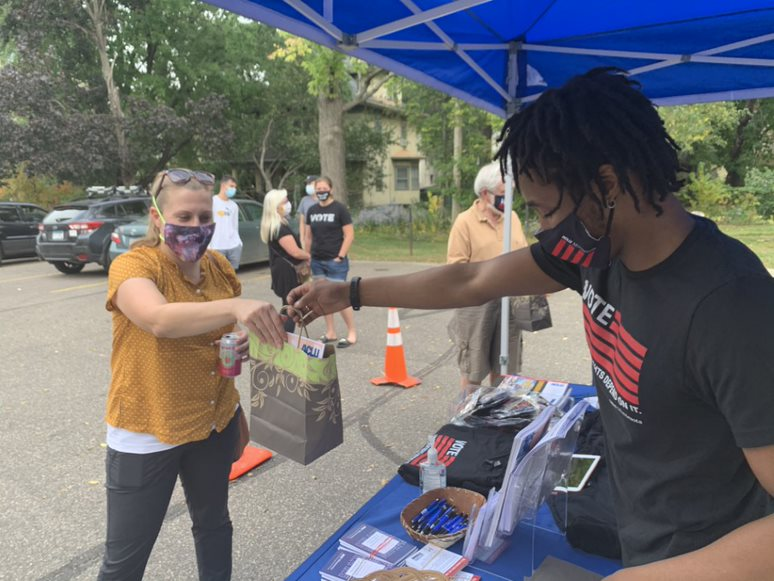 ACLU-MN organizer Ismael Dore hands out swag to a volunteer.