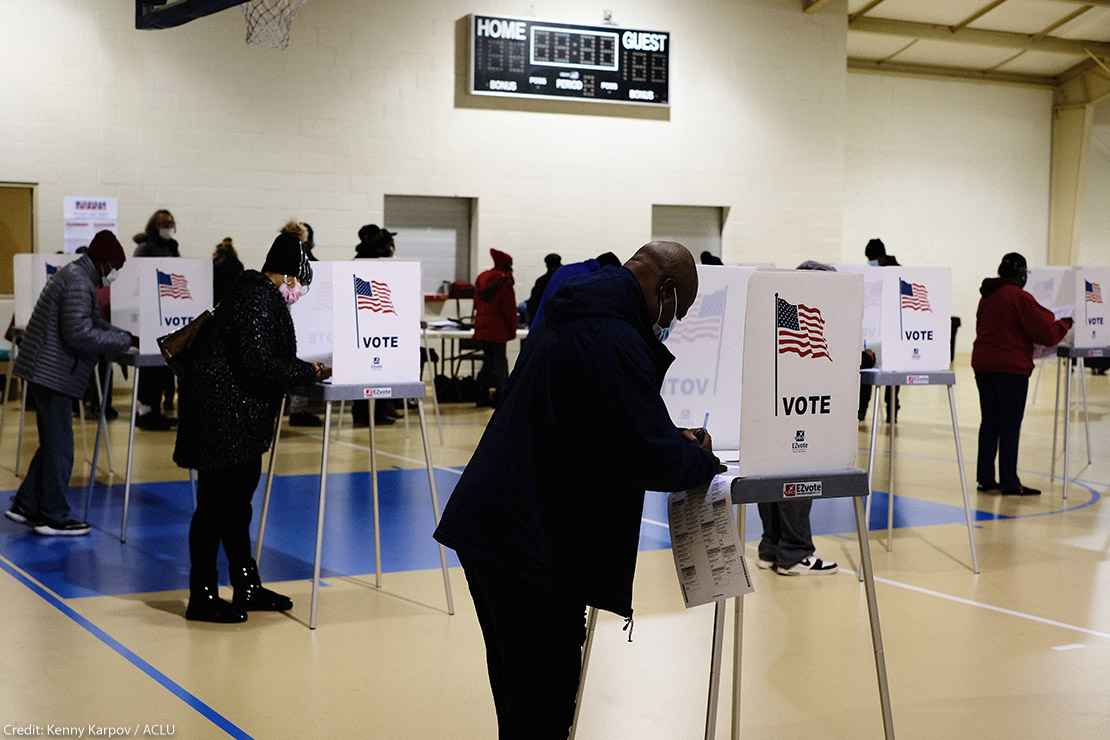 A black man filling out ballot in voting booth on Election Day.