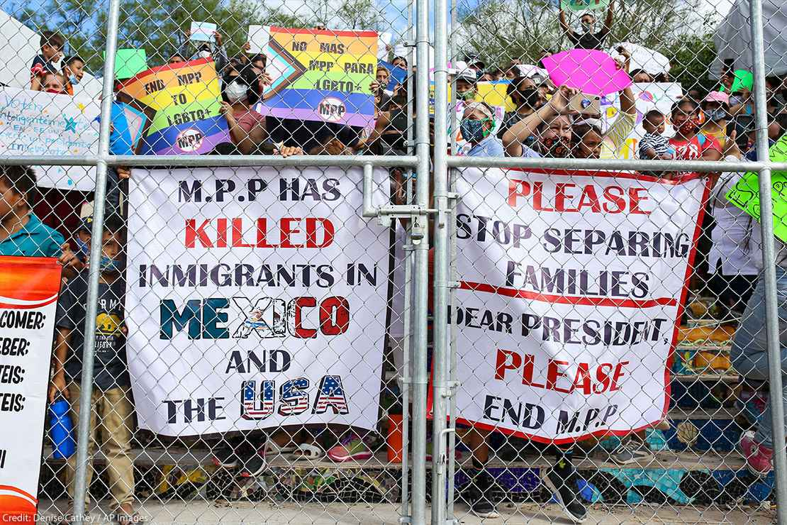 People press signs against a closed gate to the migrant encampment, asking then President Donald Trump to end the Migrant Protection Protocols during a rally at the encampment in Matamoros, Tamaulipas, Mexico on October 25, 2020.