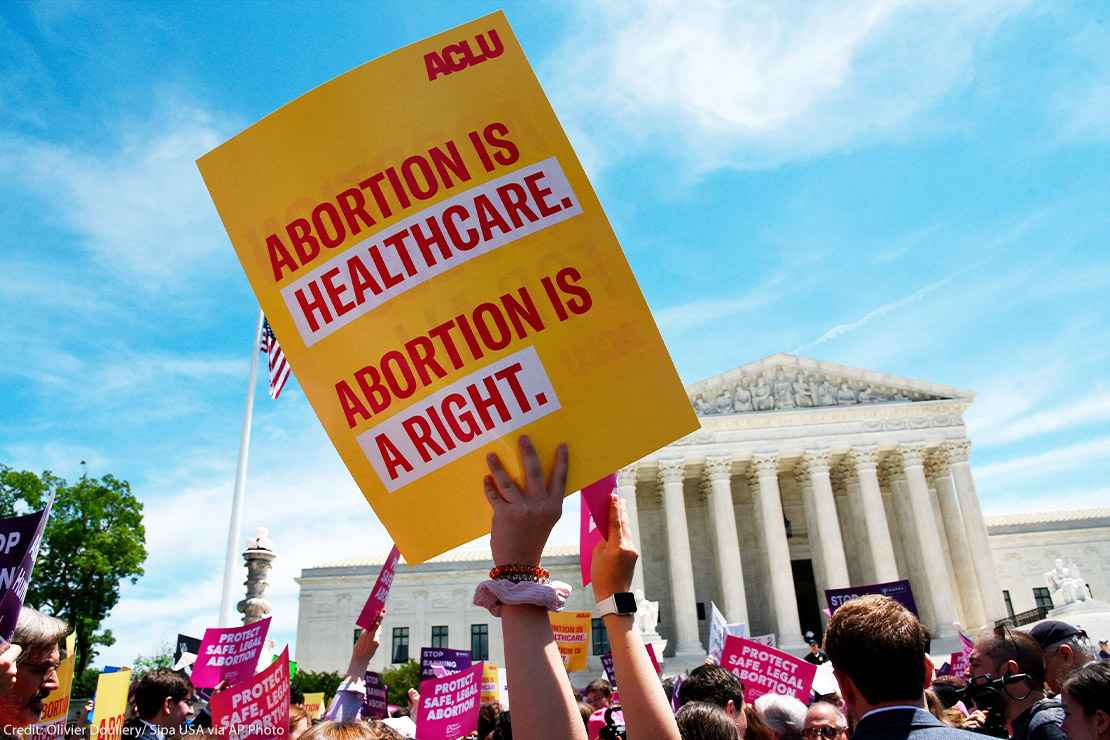 """Pro-abortion activist holds ACLU placard that reads """"Abortion is healthcare. Abortion is a right."""" during a rally at the Supreme Court"""