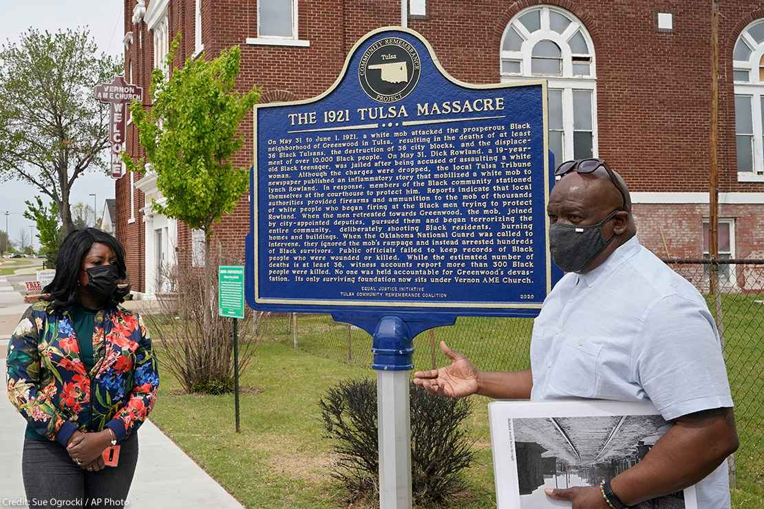 """Two people explaining a sign that reads """"the 1921 Tulsa Massacre"""" commemorating the original Black Wall Street"""