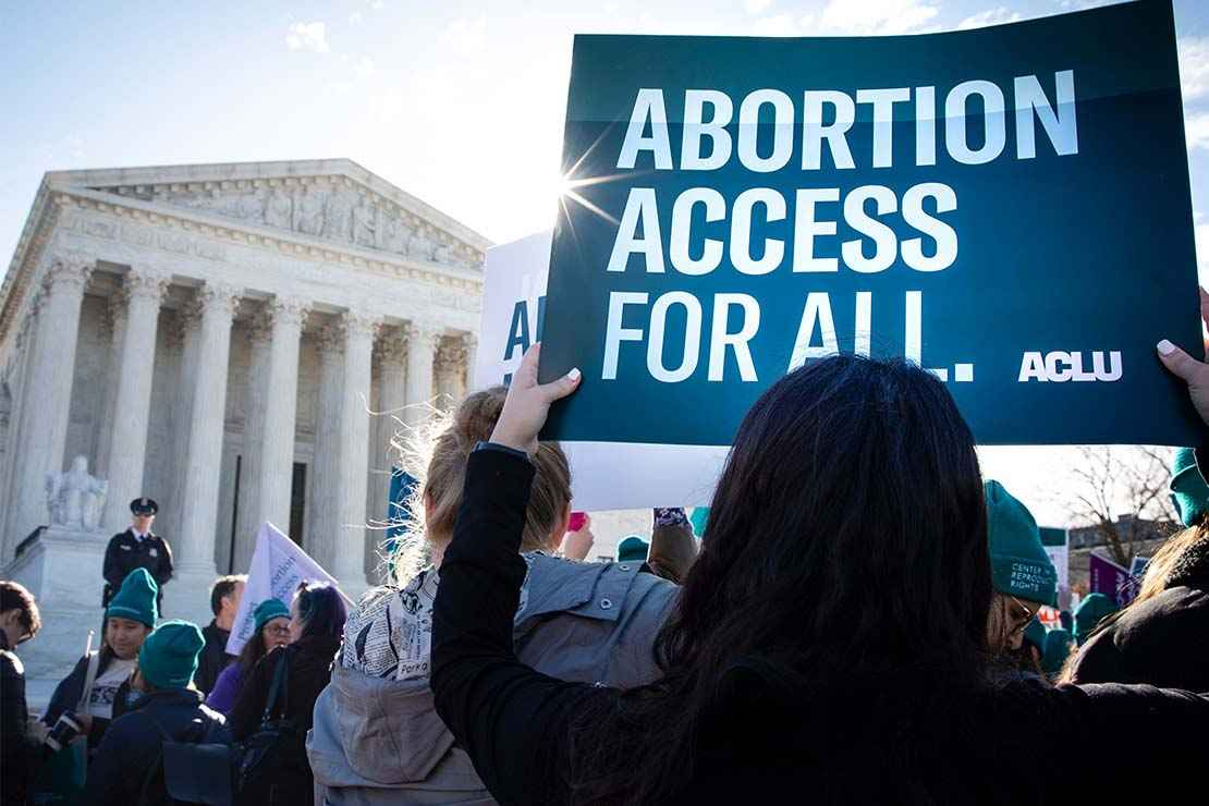 "A protestor holds aloft a sign that says ""Abortion Access for All"" in front of the Supreme Court building in Washington, DC"