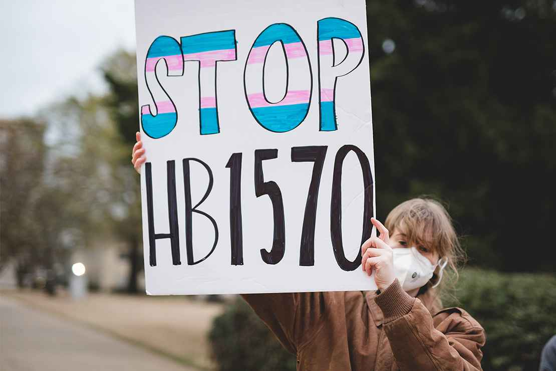 """A demonstrator holding a sign with the text """"Stop HB1570."""""""