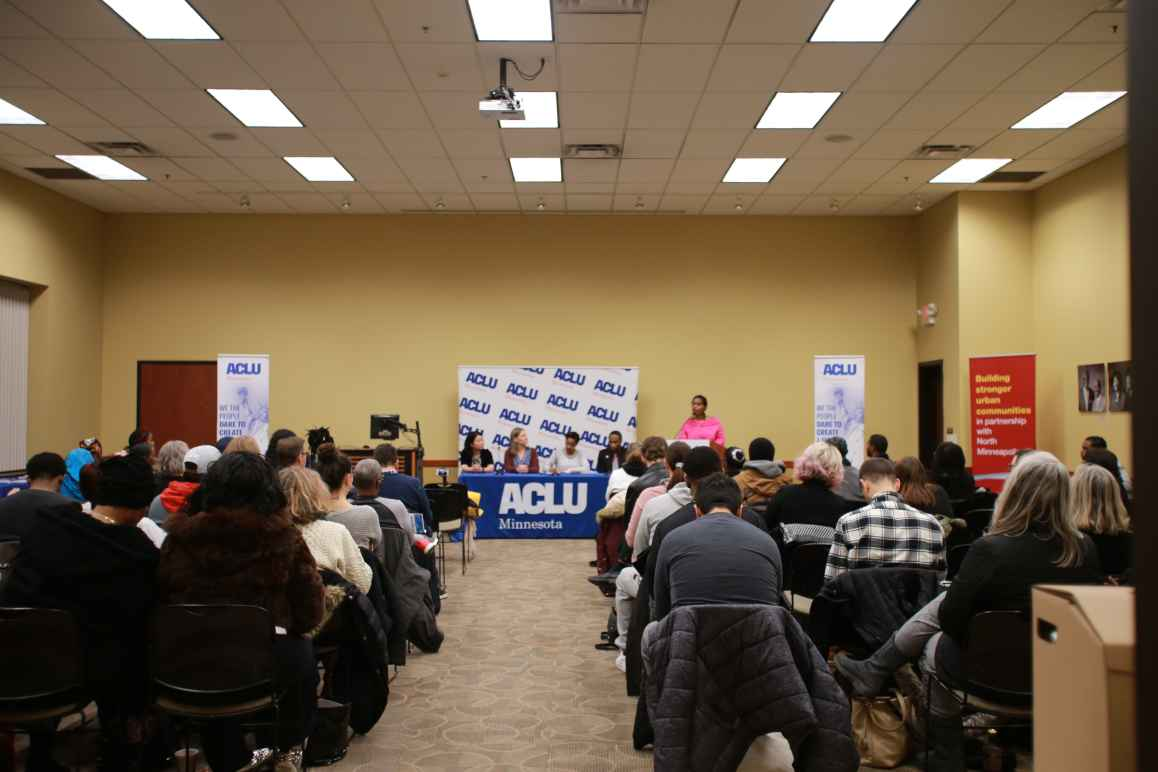 Minneapolis NAACP President Leslie Redmond speaks at a town hall event, where ACLU staff also participated. View is from the back of the room, towards the panelists' table.