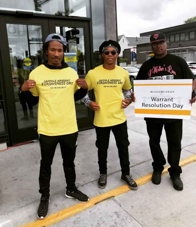 "A team of volunteers outside the event displays their yellow event t-shirts which read: ""Juvenile Warrant Forgiveness Day: Ask me for help"""