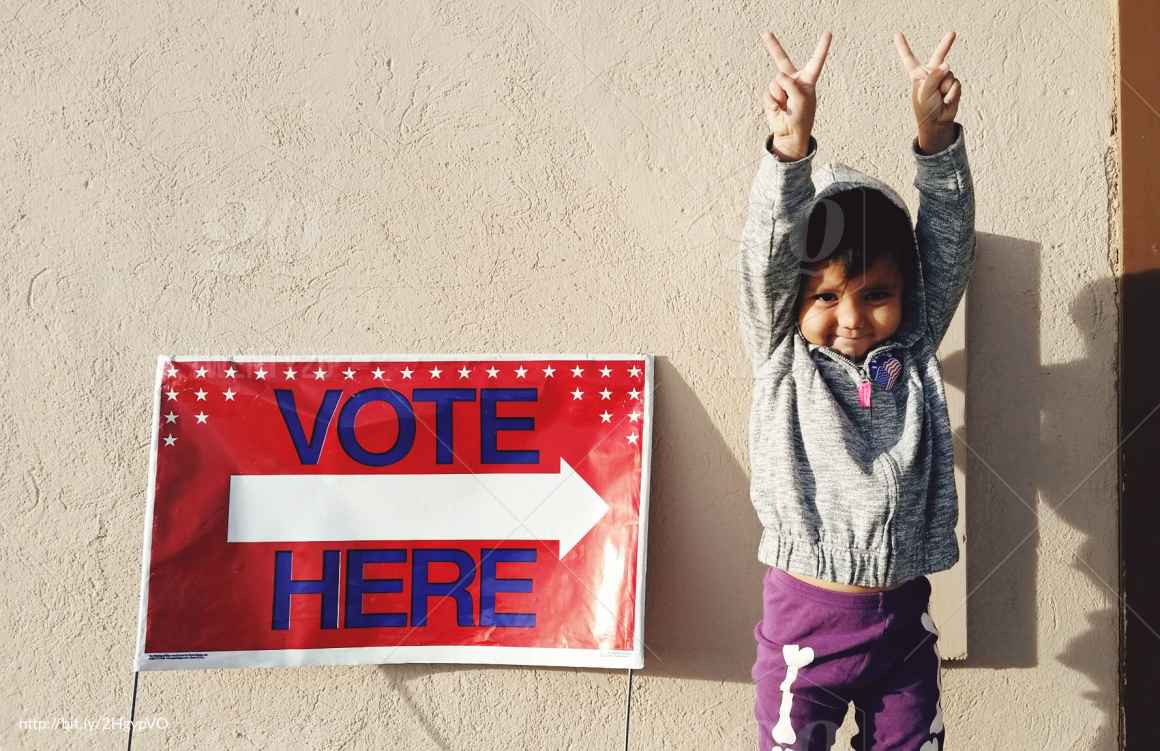child next to a vote here sign